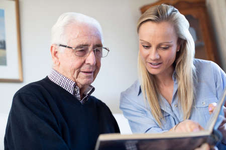 Grandfather Looking At Photo Album With Adult Granddaughter