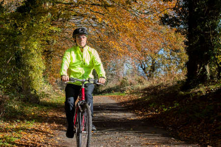 Mature Man Cycling Along Autumn Country Road