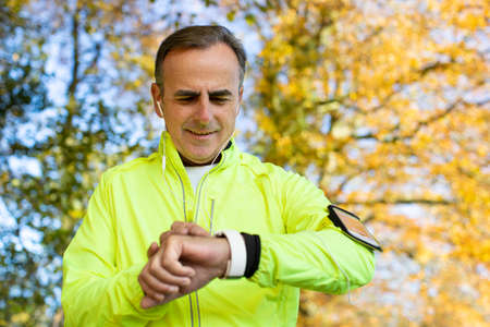 Mature Man Exercising In Autumn Woodland Looking At Activity Tracker On Smart Watch