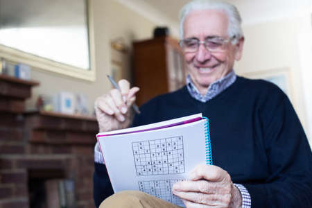 Senior Man Doing Sudoku Puzzle At Home