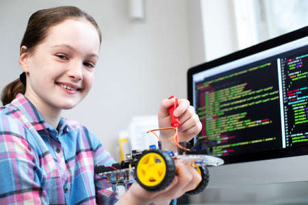 Portrait Of Female Pupil Building Robotic Car In Science Lesson Stock Photo