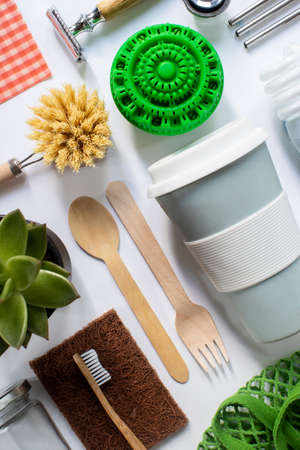 Flat Lay Shot Of Plastic Free Eco Products With Reusable Or Sustainable Zero Waste Products On Wooden Background With Metal Staws Wooden Cutlery Paper Bag Glass Jar Wax Wrapping Paper