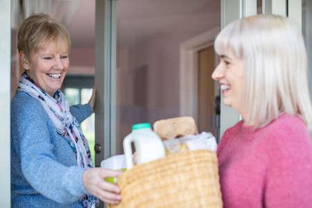 Female Neighbor Helping Senior Woman With Shopping Whilst Self Isolating During Coronavirus