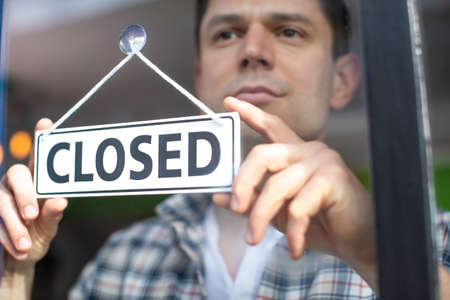 Small Business Owner With Serious Expression Putting Up Closed Sign During Recession Or Health Pandemic