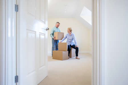Senior Couple Downsizing In Retirement Carrying Boxes Into New Home On Moving Day Foto de archivo