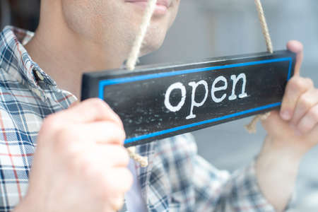 Close Up Of Smiling Male Small Business Owner Turning Around Open Sign On Shop Or Store Window Or Door