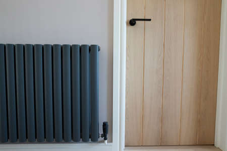 Close Up Of Closed Wooden Door And Stylish Central Heating Radiator In Modern Home
