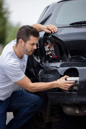Unhappy Male Driver Inspecting Damaged Car After Accident