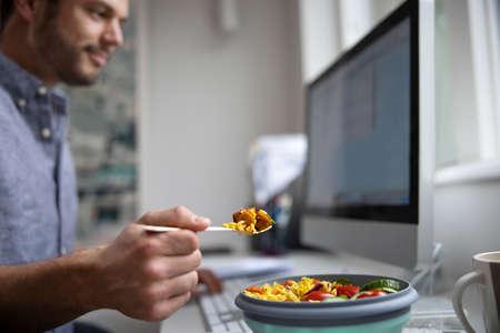 Male Worker In Office Having Healthy Vegan Lunch At Desk