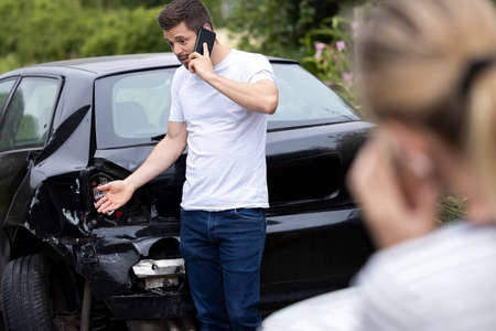 Male Driver On Phone Call To Insurance Company After Accident With Female Motorist