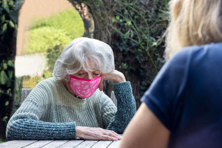Mature Woman Wearing Mask Visiting Lonely Depressed Senior Mother In Garden During Lockdown