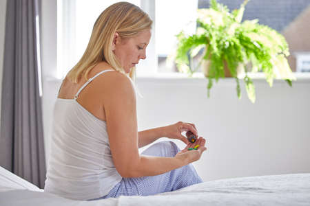 Mature Woman Sitting On Bed Wearing Pyjamas Taking Medication