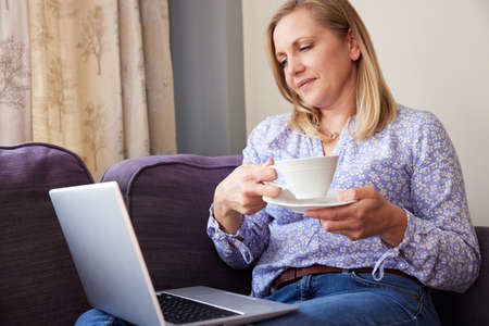 Mature Woman Sitting On Sofa Look At Laptop And Drinking Hot Drink 免版税图像