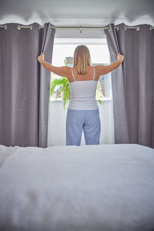 Rear View Of Woman Wearing Pyjamas Opening Curtains And Looking Out Of Window In Morning