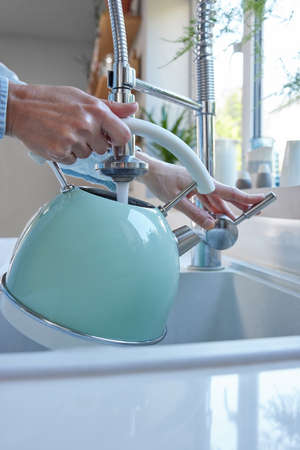 Close Up Of Woman Carefully Filling Kettle From Tap And Saving Water