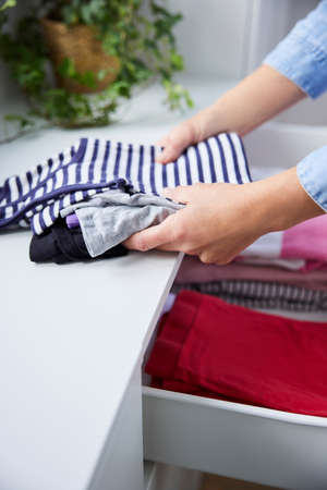 Close Up Of Woman Folding Up Clothes And Tidying Them Into Drawers 免版税图像
