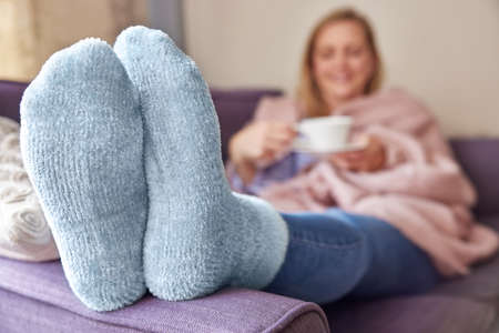 Woman At Home Wearing Cosy Warm Socks And Wrapped In Blanket Lying On Sofa Drinking Cup Of Tea