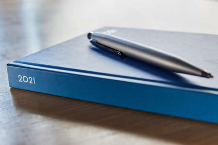 Close Up Of Pen Resting On 2021 Desk Diary On Table