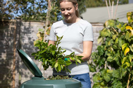 Woman Putting Garden Waste Into Composter At Home Stock fotó