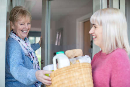 Female Neighbor Helping Senior Woman By Delivering Shopping At Home