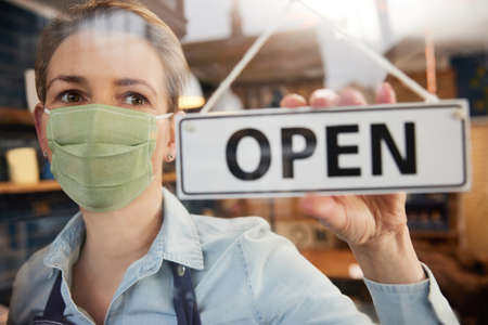 Female Owner Of Small Business Wearing Face Mask Turning Round Open Sign During Health Pandemic