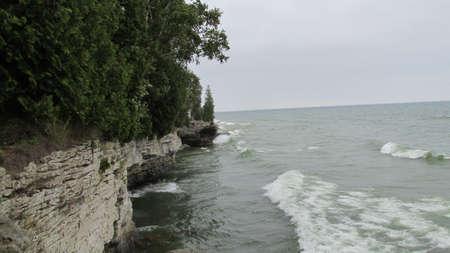 Rolling waves crashing into limestone cliff