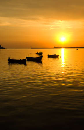 Sea, the silhouettes of boats and a beautiful sunset photo