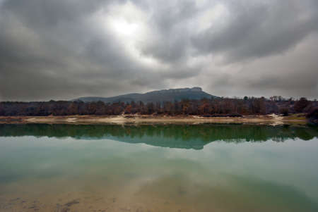 A small mountain lake on a cloudy day. Calm water, like a mirror reflects trees and mountains photo