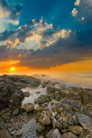 Natural sea sunset on the background of rocks Stock Photo