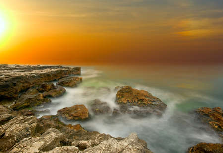 Natural sea sunset on the background of rocks and storm Stock Photo - 11667377