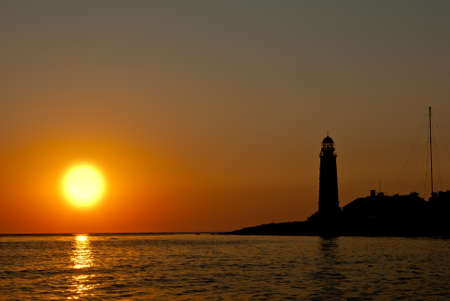 Silhouette of a lighthouse on the background of a large setting sun photo
