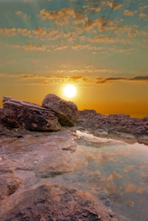 Natural sunset at the seaside  Surface water and rocks photo