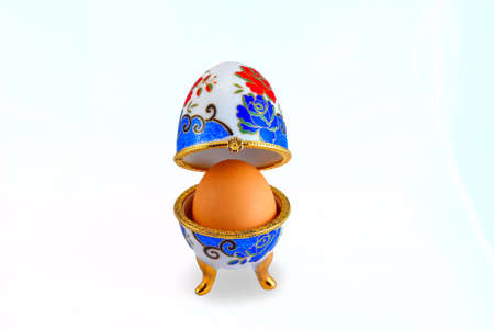 Decorative ceramic easter egg with real chicken egg against white background. photo