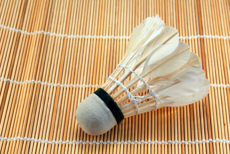 Made by hand for badminton shuttlecock against a wooden floor mat Stock Photo