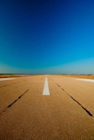 Spare the runway stretches into the distance against the blue sky Stock Photo