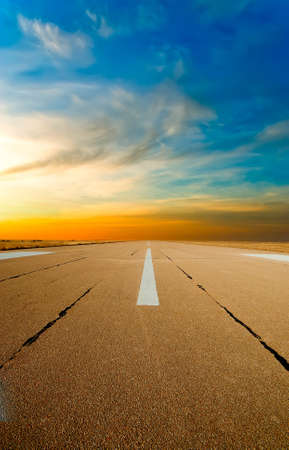Spare the runway stretches into the distance at sunset