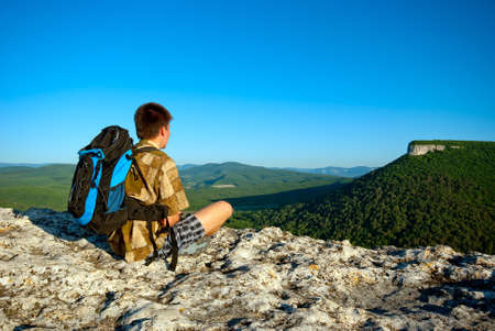 Young man with backpack sits on a rock and looks into the distance photo
