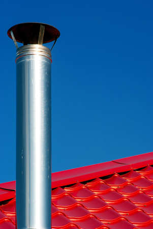 Chimney on a background of red roof and blue sky