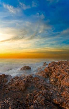 Frozen sea against sharp rocks at sunset