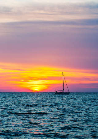 reddening: Silhouette of a yacht on the background of the last rays of sunset