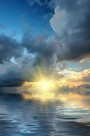 The dramatic sky and sun rays at sunset on the sea background Stock Photo
