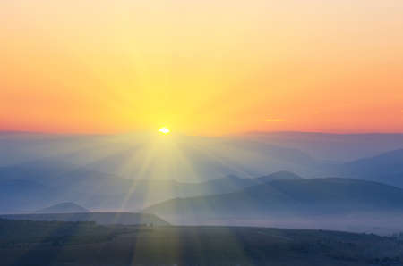 The sun with rays rises over the mountains. natural landscape Stock Photo