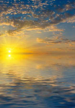 Beautiful colorful sunrise with rays of the sun above the sea