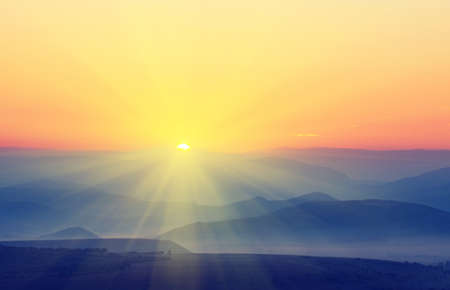The sun with rays rises over the mountains. Vintage picture Stock Photo