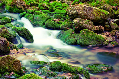 The picturesque mountain stream in the background of the stones with moss. Vintage style photo