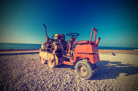Old Roller (paver) prepare the ground for the laying of asphalt. Vintage style photo