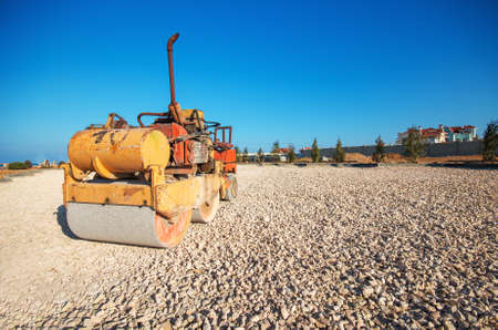 Old Roller (paver) prepare the ground for the laying of asphalt and blue sky photo