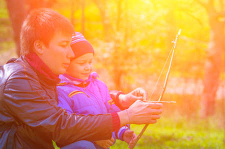 bowstring: Dad teaches his son to shoot a bow, which they did together against the bright sun in the park. family composition Stock Photo