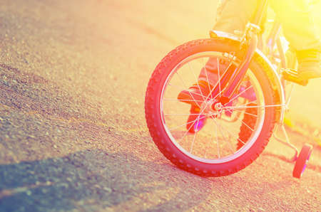 Part of the childrens bicycles and child on the background of the asphalt when it is backlit. Vintage composition