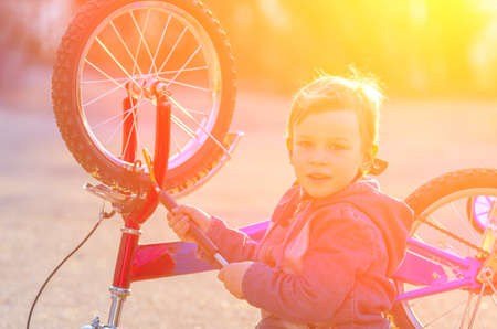 Little boy is pumped European wheel of his bike, sitting on the pavement and smiling against a bright setting sun. natural composition